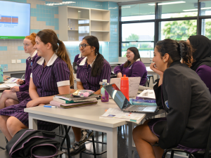 Six female Southern Cross Grammar students listening to their teacher in the upgraded STEM lab.